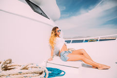 Young beautiful girl sitting on a yacht at sea relaxing on the water. Stock Photo