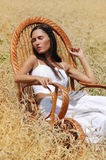Young beautiful girl sleeping in a chair in the field of wheat. Young beautiful girl with book sleeping in a chair in the field of wheat Royalty Free Stock Photo