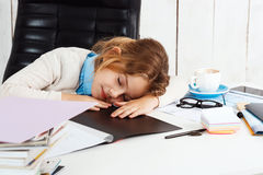 Young beautiful girl sleeping at working place in office. Young beautiful blonde girl sleeping at working place in office Stock Images