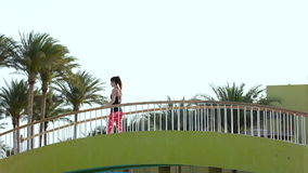 A young beautiful girl is slowly walking along the pedestrian bridge at the resort. Slim athletic brunette. Good morning stock video footage