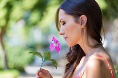 Young beautiful girl smells flowers, against green summer garden Royalty Free Stock Image