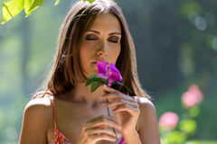 Young beautiful girl smells flowers, against green summer garden Stock Images
