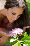 Young beautiful girl smells flowers, against green summer garden Royalty Free Stock Images