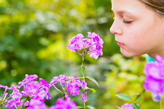 Young beautiful girl smells purple flowers in the garden. Shallow depth of field Royalty Free Stock Photo