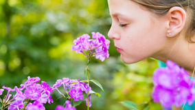 Young beautiful girl smells purple flowers in the garden. Shallow depth of field Royalty Free Stock Photography