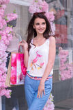 Young beautiful girl smiles after shopping with bags in hands Stock Photography