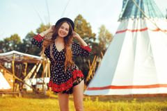 Young beautiful girl smiling on background teepee, tipi- native indian house. Pretty girl in hat with long cerly hair. In dress. Travel in Western. Freedom stock photography