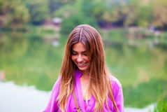 Young beautiful girl smiling in the park. The purple blouse. Happy woman laughing in the forest. A girl in a bright shirt Royalty Free Stock Images