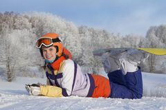 Young beautiful girl snowboarder resting on ski slope, she`s lyi Royalty Free Stock Photos