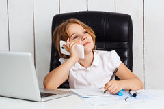 Young beautiful girl speaking phone at working place in office. Royalty Free Stock Photography