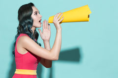 Young beautiful girl speaks in a yellow paper loudspeaker. Young beautiful girl speaks in a paper loudspeaker on a blue background royalty free stock image