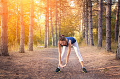 Young beautiful girl sports in the autumn forest at sunset Stock Image