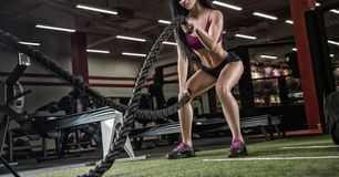 Young beautiful girl sports a bodybuilder in a modern gym traini Royalty Free Stock Photo