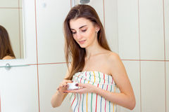 Young beautiful girl stand towel in the bathroom and holding a cream. Closeup Royalty Free Stock Photo