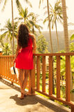 Young beautiful girl standing on the balcony at a resort in the background of the rainforest. Royalty Free Stock Photography