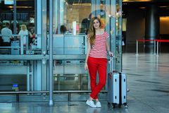 Young beautiful girl standing close up with her silver suitcase in the airport Royalty Free Stock Images