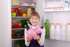 Girl standing with piggy bank money box on the refrigerator background. Young beautiful girl standing with piggy bank money box on the refrigerator background Stock Photo