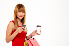 Young beautiful girl standing with purchases over white background. Royalty Free Stock Images