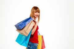 Young beautiful girl standing with purchases over white background. stock photography