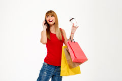 Young beautiful girl standing with purchases over white background. Royalty Free Stock Photos