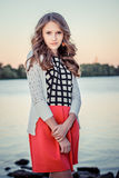 Young beautiful girl standing by the river at sunset Royalty Free Stock Photo