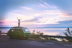 Young beautiful girl standing on the roof of old timer classic camper van parked by the sea with amazingly colorful sunset sky, ha stock image