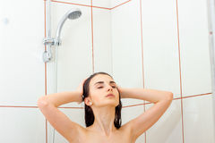 Young beautiful girl is standing under the shower closing her eyes and washes hands hair Royalty Free Stock Images