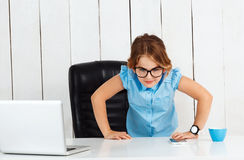 Young beautiful girl standing at working place in office. Royalty Free Stock Photo