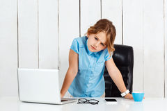 Young beautiful girl standing at working place in office. Stock Photos