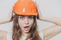 A young beautiful girl stands on a gray background. It is dressed in an orange helmet on the head. During this time he royalty free stock photos