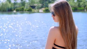 Young beautiful girl stands on the lake shore. In the sunny midday Royalty Free Stock Photo