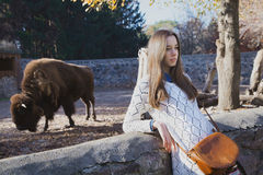 Young beautiful girl stands near the aviary with bison in city z Royalty Free Stock Image