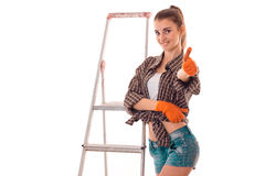 Young beautiful girl stands near ladder for repair and shows the class Royalty Free Stock Photos