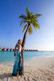 Young beautiful girl stands near by palm tree on b Royalty Free Stock Image