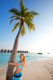 Young beautiful girl stands near by palm tree on b Royalty Free Stock Images
