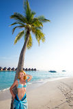 Young beautiful girl stands near by palm tree on b Stock Images