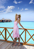 Young beautiful girl stands in pink sundress on sundeck of villa on water, Maldives Stock Image