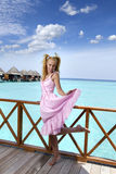 Young beautiful girl stands in pink sundress on sundeck of villa on water, Maldives Royalty Free Stock Photo