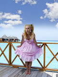 Young beautiful girl stands in pink sundress on sundeck of villa on water, Maldives Royalty Free Stock Photography