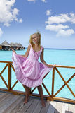 Young beautiful girl stands in pink sundress on sundeck of villa on water, Maldives Stock Photography