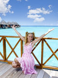 Young beautiful girl stands in pink sundress on sundeck of villa on water, Maldives Stock Photos
