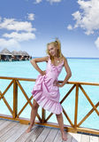 Young beautiful girl stands in pink sundress on sundeck of villa on water, Maldives Royalty Free Stock Image