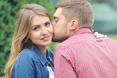 Young beautiful girl staring at camera while being kissed Stock Photography