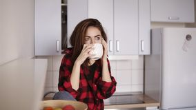 Young beautiful girl starts calling someone while sitting in her kitchen and having a cup of tea in her hand. stock footage
