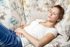 Young beautiful girl with stomach pain lying on the sofa. Stock Photography