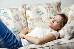 Young beautiful girl with stomach pain lying on the sofa. Royalty Free Stock Photo