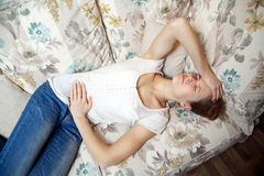 Young beautiful girl with stomach pain lying on the sofa. Stock Image