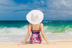 Young beautiful girl in a straw white hat back to the viewer on Royalty Free Stock Photos