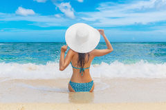 Young beautiful girl in a straw white hat back to the viewer on Stock Photo