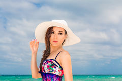 Young beautiful girl in a straw white hat on the beach of a trop Royalty Free Stock Images
